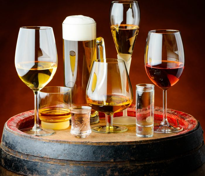 Alcoholic drinks in glasses on a wooden barrel in a cellar.